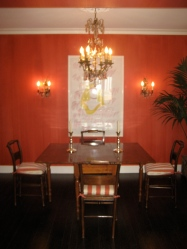 Burnt Orange striéd walls and antique sconces are juxtaposed with a piece of contemporary art.