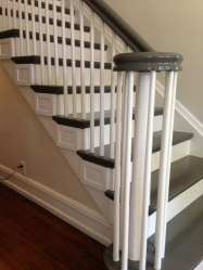 High gloss charcoal paint and added architectural details update a vintage stairway