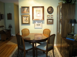 A soft sage paint color and creative arrangement of artwork cozy the dining area of a condo.