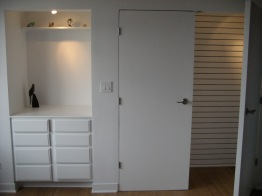 Retrofit closet with slat wall for adjustable rods and a built in chest with space for a changing cushion await a baby on the way.
