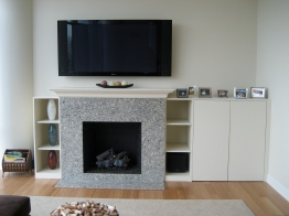 A custom ventilated cabinet, and extended mantel hide electronics and balance the family room TV.
