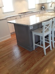 Charcoal gray painted island creates a nice contrast with the white cabinets.