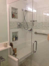 A sleek shower with a bench replaced an old tub so the owner could age in place gracefully!