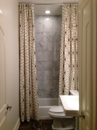 The view from the front door is of the guest bath, so why not make it dramatic with 10 ft long shower curtain draperies!