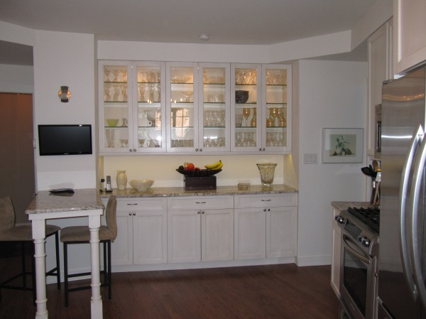The original butler's pantry was integrated into the triangular shaped kitchen with beautifully lit glass upper cabinets.