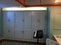 Built in storage and fold down desks help this basement playroom do double duty.
