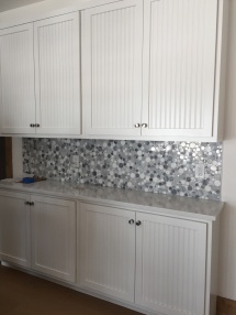 White beadboard cabinets around the perimeter and navy cabinetry for the island and peninsula