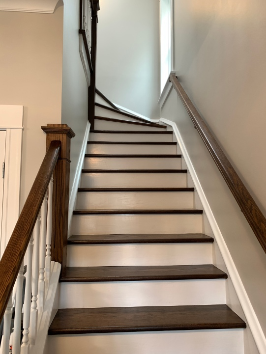 Darker stained stairway treads and railings brightened up with white risers and spindles.